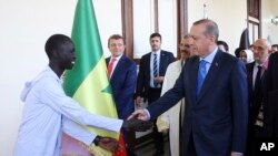 Turkey's President Minister Recep Tayyip Erdogan shakes hands with an African student as he arrives to receive a honorary doctorate from Medical Sciences University in Istanbul, Sunday, Nov. 6, 2016.