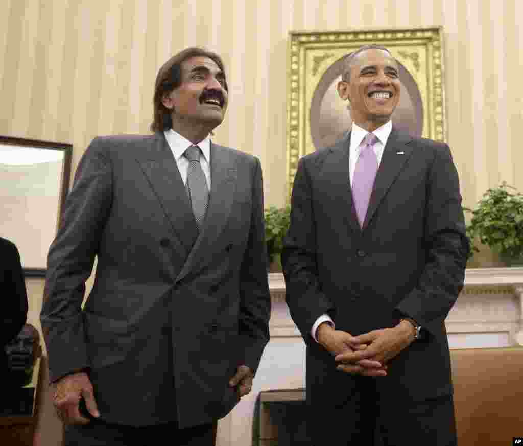 President Barack Obama, right, stands with Sheik Hamad bin Khalifa al-Thani of Qatar following their meeting in the Oval Office of the White House in Washington, April 23, 2013.