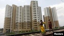 ແມ່ຍິງຄົນນຶ່ງເຈ່ຍລູກ ຍ່າງນຳໜ້າຜົວຂອງນາງ ຜ່ານຕຶກອາຄານຫໍພັກ ທີ່ພວມຢູ່ໃນລະຫວ່າງການກໍ່ສ້າງໃນເຂດຊານ ເມືອງ ນະຄອນ Kolkata ປະເທດອິນເດຍ (26 ເມສາ 2012)