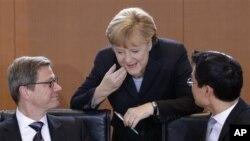 Dari kiri: Menteri Luar Negeri Jerman Guido Westerwelle, Kanselor Angela Merkel dan Menteri Perekonomian Jerman Philipp Roesler, berbincang setibanya di ruang sidang kabinet untuk pertemuan mingguan di Berlin, Jerman (6/12). Kabinet Jerman telah menyetujui misi pengiriman misil patriot ke Turki.