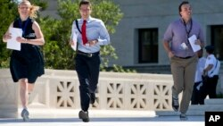 FILE - Interns run with a decision across the plaza of the Supreme Court in Washington, D.C., June 29, 2015. Some students in the U.S. defer college for a year, trying instead to gather life and work experiences in other environments.