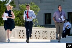 New interns run with a decision across the plaza of the U.S. Supreme Court in Washington on June 29, 2015. (Photo by Jacquelyn Martin/AP)