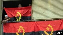 Une famille angolaise derrière le drapeau national à Luanda, le 9 janvier 2010.