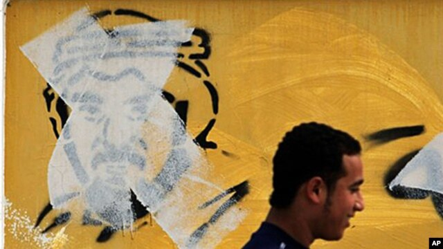 A Bahraini man  in Manama passes by an image of Shiite leader Hassan Meshaima, crossed out with a paint roller by authorities, February 24, 2011