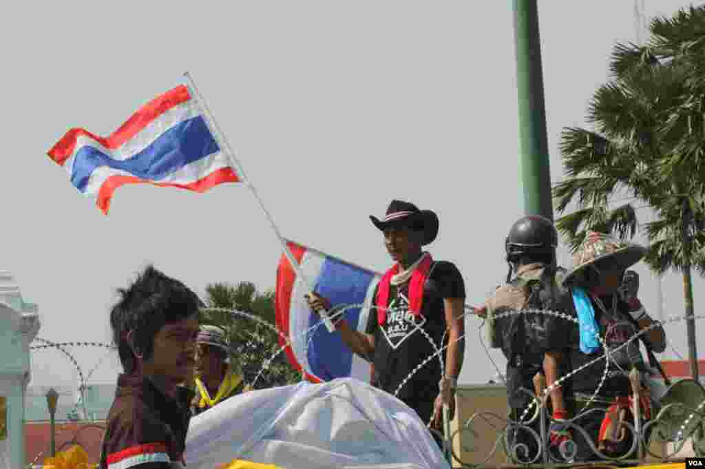 A protester waves a Thai flag at the entrance of Government House after barricades were taken down, Bangkok, Dec. 3, 2013. (Steve Herman/VOA)