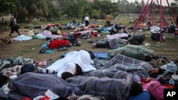 """Dozens of Central American migrants, traveling with the annual """"Stations of the Cross"""" caravan, sleep at a sports club in Matias Romero, Oaxaca State, Mexico, April 3, 2018. The caravan of Central American migrants that angered U.S. President Donald Trump was sidelined at a sports field in southern Mexico with no means of reaching the border even as Trump tweeted another threat to Mexico Tuesday. (AP Photo/Felix Marquez)"""