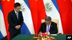 El ministro de Relaciones Exteriores de El Salvador, Carlos Castañeda, (derecha) firma documentos en una ceremonia para el establecimiento de relaciones diplomáticas de El Salvador con China, en Beijing, el martes, 21 de agosto de 2018.