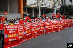 """Người biểu tình với biểu ngữ ghi dòng chữ: """"Chúng tôi, nhân dân Myanmar, hoàn toàn ủng hộ mọi hành động mà LHQ và Hoa Kỳ có thể đề ra chống """"Độc tài Khủng bố"""" trong cuộc biểu tình chống đảo chính quân sự. Ảnh chụp trước Ngân hàng Kinh tế Myanmar ở Mandalay, Myanmar, ngày 15/2/2021. AP"""