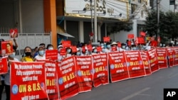 """Protesters hold banners that read """"We Myanmar People fully support every action that U.N. and U.S. will take on Terrorist Dictatorship"""" during an anti-coup rally in front of the Myanmar Economic Bank in Mandalay, Myanmar on Monday, Feb. 15, 2021."""