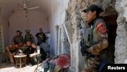 Seorang serdadu berjaga-jaga saat beberapa perwira dari unit kontraterorisme Irak menonton video yang dipancarkan dari drone dalam sebuah rapat dengan pasukan Irak di garis depan di Kota Tua Mosul Barat, Irak, 27 Juni 2017 (foto: REUTERS/Erik De Castro)