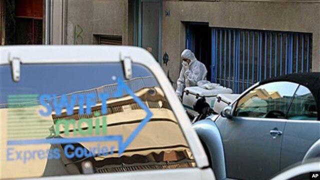 A Greek anti-terrorist police officer investigates a private delivery company after an explosion in Athens, 1 Nov 2010