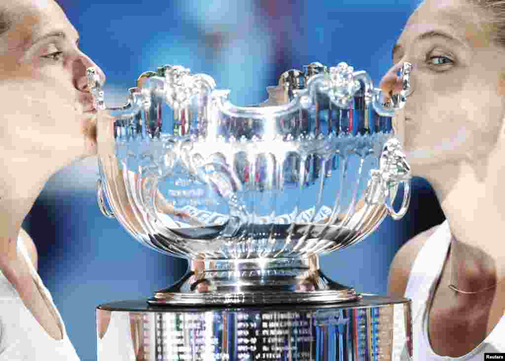 Sara Errani (R) and Roberta Vinci of Italy kiss their trophy after defeating Ashleigh Barty and Casey Dellacqua of Australia in their women's doubles final match at the Australian Open tennis tournament in Melbourne.