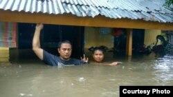 Warga berusaha mengungsi dari rumahnya yang terendam banjir di Bima, NTB Rabu 21/12 (foto: BNPB).