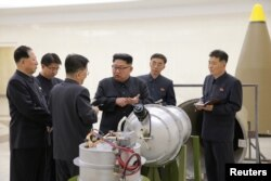 North Korean leader Kim Jong Un, center, provides guidance on nuclear weapons development in this undated photo released by North Korea's Korean Central News Agency in Pyongyang, Sept. 3, 2017.