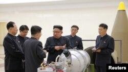 Lidè Kore di Nò a, Kim Jong Un, nan mitan, nan moman li tap bay lòd ak konsyè sou devlopman zam nikleyè ak wo eta majò lame peyi li a. Foto Pyongyang pibliye nan dat 3 septanm 2017.