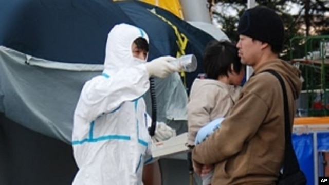 A man and his child who have just arrived from inside the danger zone in Fukushima Prefecture are checked for abnormal radiation levels, Sunday, 13 March 2011