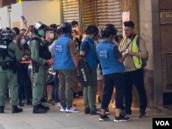 香港警方6月28日下午在旺角登打士街展开大围捕,传媒联络队人员检查采访期间被封锁线围困记者的证件才放行。 (美国之音/汤惠芸)
