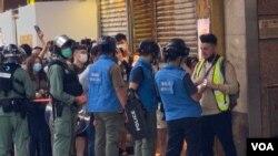香港警方6月28日下午在旺角登打士街展開大圍捕,傳媒聯絡隊人員檢查採訪期間被封鎖線圍困記者的證件才放行。(美國之音湯惠芸)