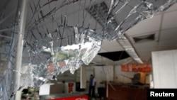 卡拉卡斯社區遭到哄搶後,可以看到一個便利店破損的窗戶(2017年4月21日)