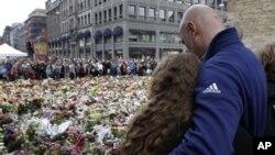 ہلاک ہونے والوں کی یاد میں لوگ پھول چڑھا رہےہیں