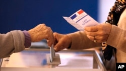 Voters cast their ballot in the regional elections, Dec. 13, 2015, in Nice, southeastern France.