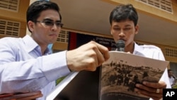 """Dy Khamboly, left, a staff member at the Documentation Center of Cambodia, helps a student read his book """"A History of Democratic Kampuchea"""" in Anlong Veng, in Oddar Meanchey province, file photo."""