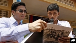"Dy Khamboly, left, a staff member at the Documentation Center of Cambodia, helps a student read his book ""A History of Democratic Kampuchea"" in Anlong Veng, in Oddar Meanchey province."