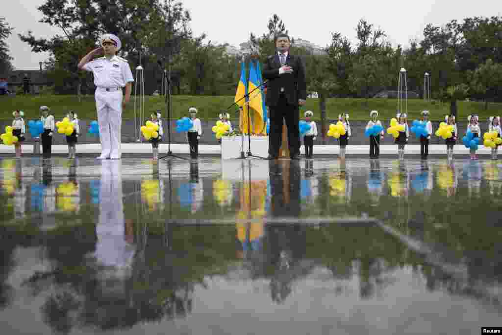 Ukraine's President Petro Poroshenko listens to the national anthem during Independence Day celebrations, in the Black Sea port of Odessa, Aug. 24, 2014.