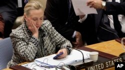 FILE - In this March 12, 2012, file photo, then-Secretary of State Hillary Clinton checks her mobile phone after her address to the Security Council at United Nations headquarters. The FBI released another batch of emails Oct. 21, 2016.