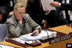 FILE - Then-Secretary of State Hillary Clinton checks her mobile phone after addressing the U.N. Security Council, March 12, 2012.