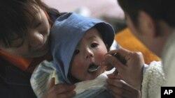 Seorang perempuan menggendong bayinya sementara saudaranya menyuapinya makanan di Yamada, Jepang. (Foto: Dok)