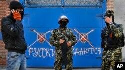 Dân quân thân Nga đứng trước một cánh cổng với hàng chữ 'Nga không đầu hàng' tại Slovyansk, miền đông Ukraine, ngày 25/4/2014.