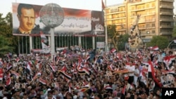 A handout picture released by the Syrian Arab News Agency (SANA) shows hundreds of Syrians waving their national flag during a rally, July 28, 2011