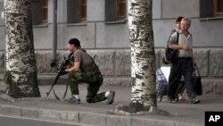 11일 우크라이나 동부 도네츠크 지역에서 한 정부군 병사가 쇼핑몰 앞에서 경계근무를 서고 있다.