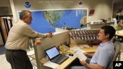 National Hurricane Center director Bill Read, left, talks with meteorologist Wallace Hogsett, Monday, Aug. 22, 2011 at the National Hurricane Center in Miami.
