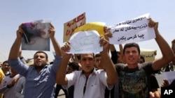 Warga Irak dari komunitas Yazidi meneriakkan slogan anti militan Islam di depan markas besar PBB meminta perlindungan internasional di Irbil, Irak, Senin, 4 Agustus 2014.