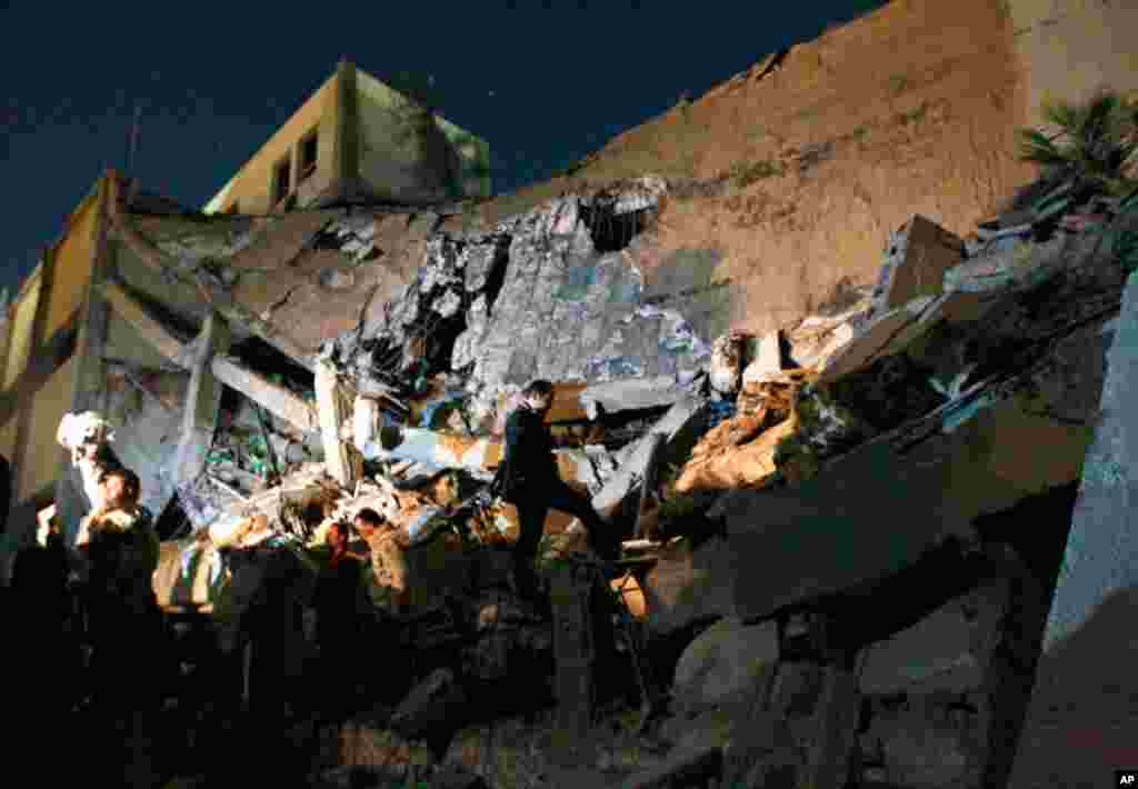 Libyan soldiers survey the damage to an administrative building hit by a missile, March 20, 2011, in the heart of Gadhafi's Bab Al Azizia compound in Tripoli. (AP/Jerome Delay)