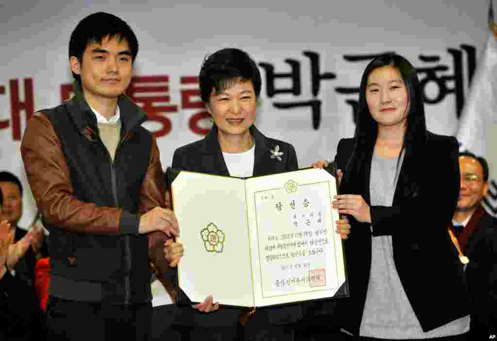 South Korea's president-elect Park Geun-hye, center, poses with an official certificate stating her election victory, Seoul, December 20, 2012.