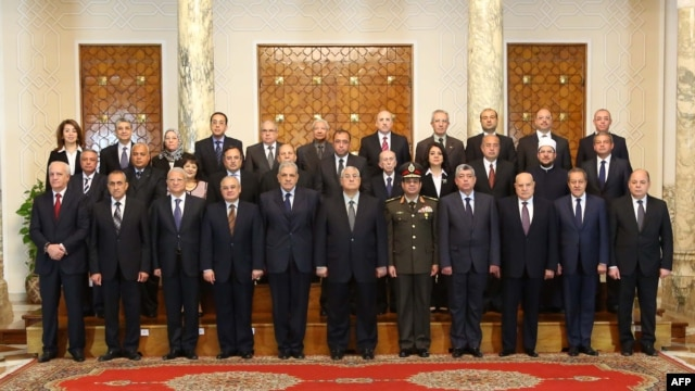 A handout picture made available by the Egyptian presidency shows Egypt's interim president Adly Mansour (C) posing with the newly-appointed cabinet members during the swearing in ceremony at the presidential palace in Cairo, Mar, 1, 2014.