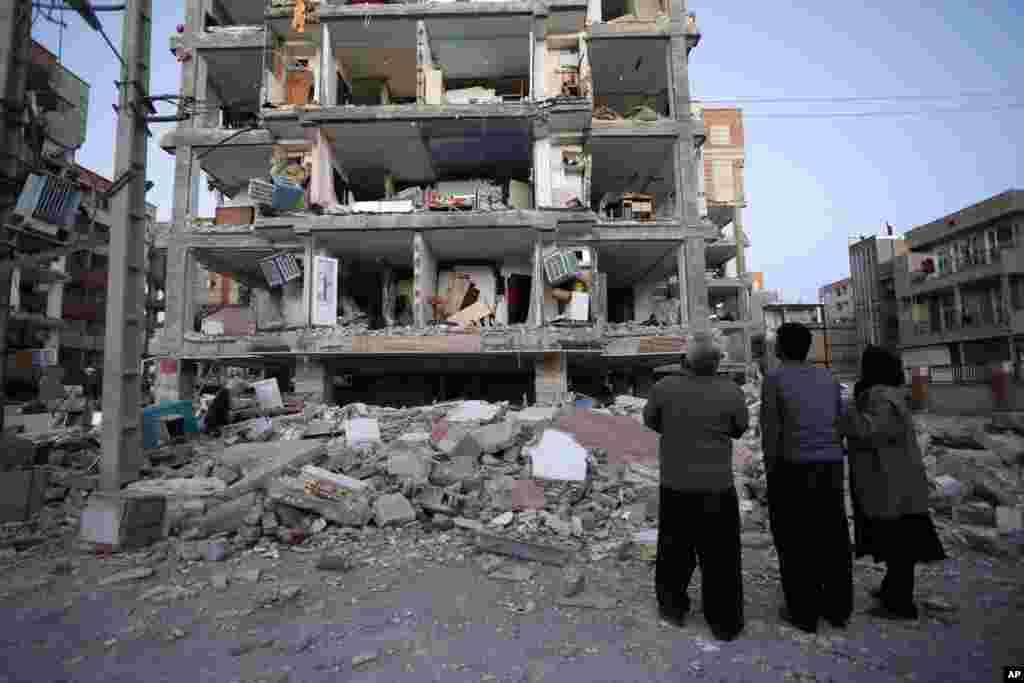 Sur cette photo fournie par l'ISNA, les habitants regardent les bâtiments détruits après un tremblement de terre dans la ville de Sarpol-e-Zahab dans l'ouest de l'Iran, lundi 13 novembre 2017.