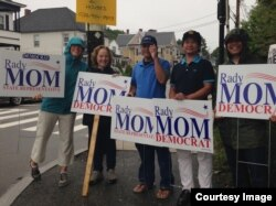 Supporters of Democratic Party candidate Rady Mom recently holding campaign signs.