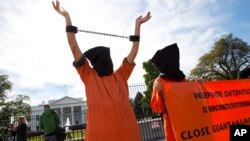 FILE - People protest at the White House in Washington against continuing detentions at the Guantanamo Bay center and Bagram prison, Oct. 24, 2014.