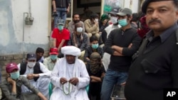 Mama Qadeer Baluch, wearing a white turban, chairman of the Voice for Baluch Missing Persons, waits to start a march with protesters in Rawalpindi, Pakistan, Feb. 27, 2014.