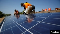 Des techniciens travaillent sur un panneau solaire, Mission Viejo, Californie, le 25 octobre 2013