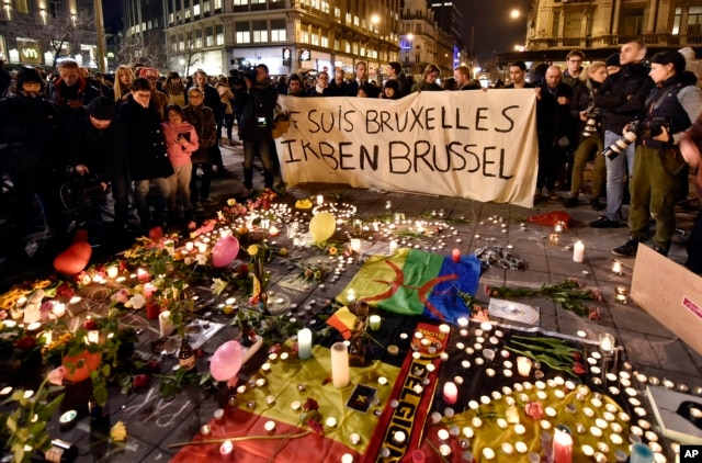 "People holding a banner reading ""I am Brussels"" behind flowers and candles to mourn for the victims at Place de la Bourse in the center of Brussels, March 22, 2016."