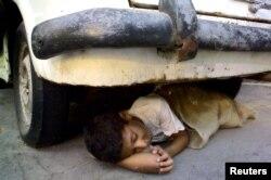 Seorang anak tunawisma Mesir tidur di bawah sebuah mobil tua berkarat di sebuah jalan di Kairo, 20 Agustus 2004. (Foto: Reuters)