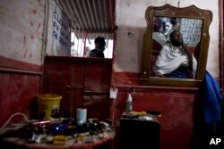 Peter Jean-Baptiste, gets a haircut and a shave in the barbershop of his brother Phillippe Jean-Baptiste in Canaan, June 21, 2015.