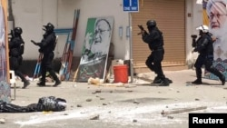 FILE - This image provided by an activist who requested to remain unnamed shows Bahraini security forces during a raid on a sit-in demonstration, in Diraz, Bahrain, May 23, 2017.