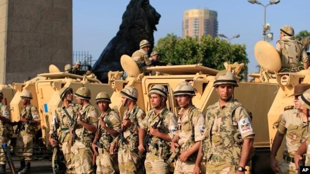 Binh sĩ Ai Cập đứng cạnh các xe bọc thép canh gác lối vào Quảng trường Tahrir tại thủ đô Cairo, ngày 8/7/2013.