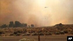 Dalam foto iyang dikirim oleh Vince O'Daye ini, nampak sebuah helikopter terbang di atas gumpalan asap dari api di kawasan yang dihuni oleh masyarakat Sutcliffe, Nevada, sekitar 56,4 kilometer sebelah utara Reno, Nevada, 30 Juli 2016. (Foto: dok).